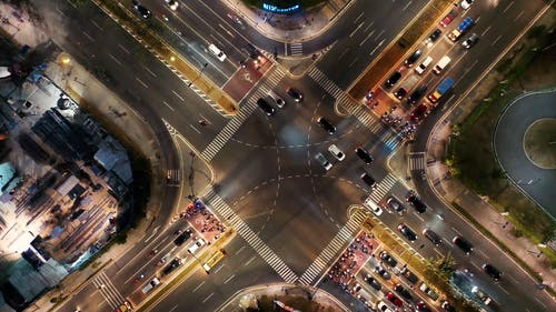 From Above Footage Of Vehicular Traffic On A Busy Street Intersection In The City At Night