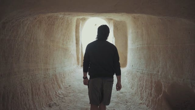 A Man Walking Out From A Man Carved Cave