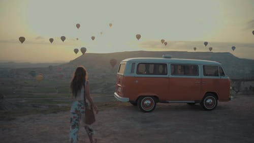 A Woman Walking Towards A Recreational Vehicle With Hot Air Balloon Festival As Backdrop