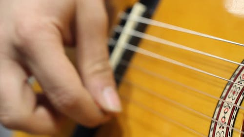A Person Strumming The Guitar String With His Fingers