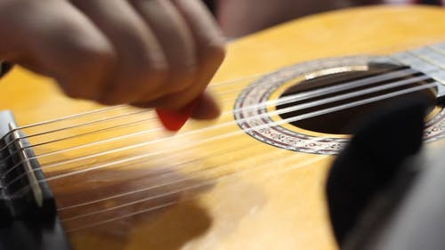 Strumming The Strings Of A Guitar With The Fingers