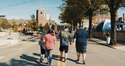 Eine Gruppe Von Menschen, Die Die Straße Entlang Gehen, Die Zu Einer Kirche Führt