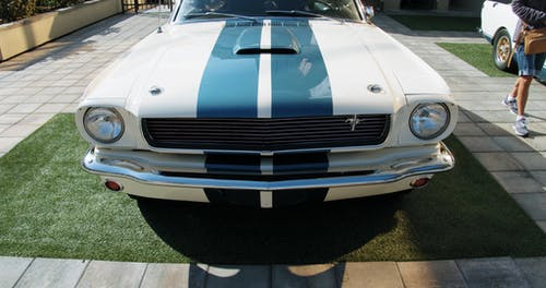 Close-up Footage Of The Front End Of A Parked Classic Mustang Car With Striped Hood