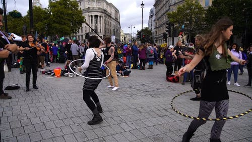 A Group Of Street Performers Performing On A Public Place