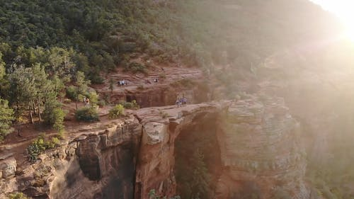 A Group Of People On Top Of A Natural Cliff Bridge Of A Rocky Mountain