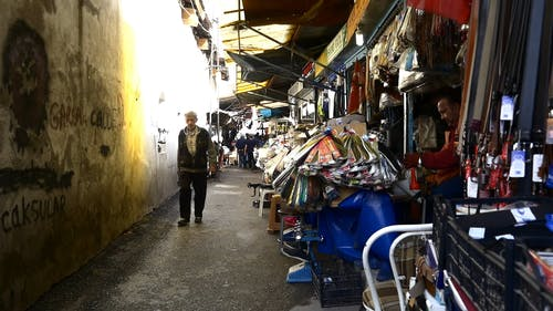 People Walking In An Alley Lined With Several Small Business Establishment Selling A Variety Merchandise