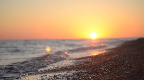 Ground Level Footage Of Waves Breaking On The Shore With The Sun Setting In The Horizon