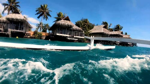 Low Angle Footage Of Cottages Along The Shoreline Of Of A Tropical Island Resort