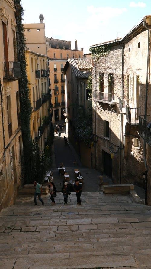 People Climbing A Stairs In A Narrow Road