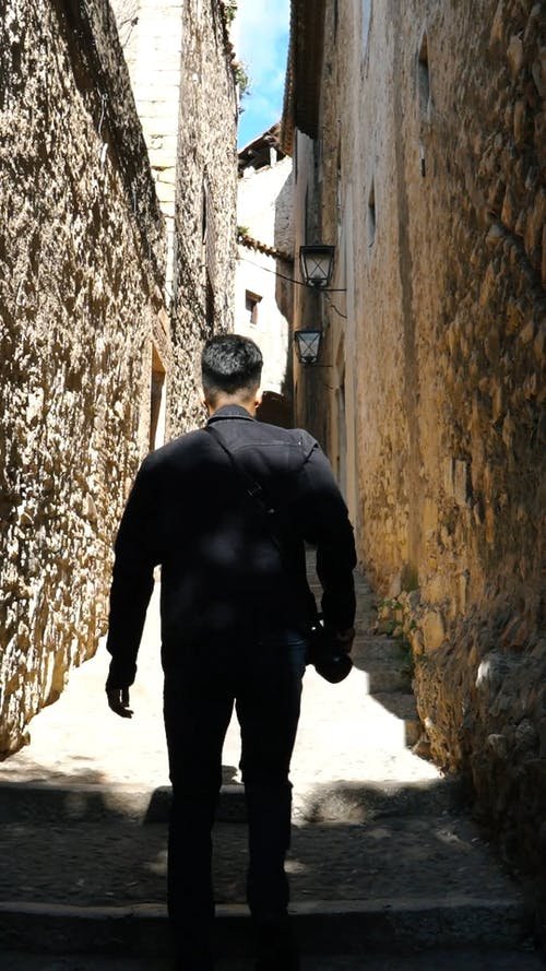 A Man Climbing The Stairs Of A Narrow Road