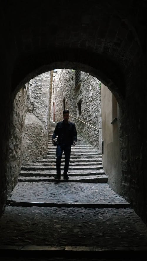A Man Walking Down A Narrow Concrete Path With Stairs Into A Tunnel