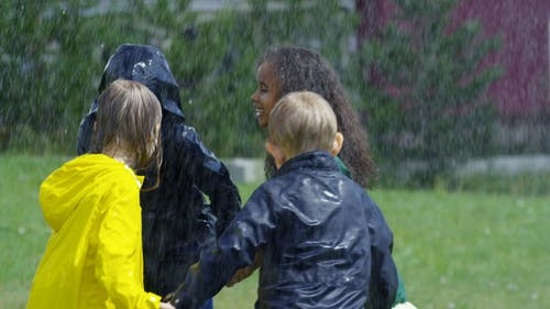 Children Playing In A Park Getting Wet By  The Rain