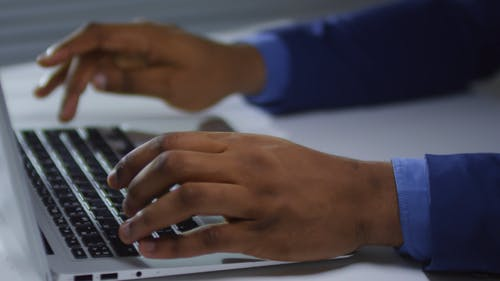 A Person Hands Typing On A Laptop Keyboard