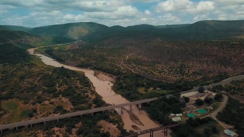 Aerial footage Of Bridges Across A River Surrounded With Hills And Mountains