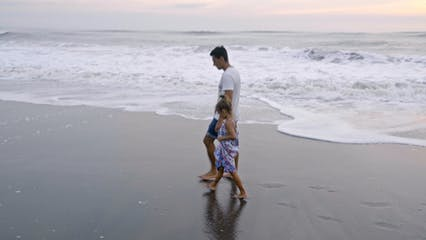 Father And Daughter Walking Along The Shore
