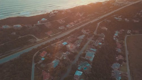 Aerial Footage A Road And Houses Close To The Waterfront With The Sun Setting On The Edge Of The Shoreline In Horizon