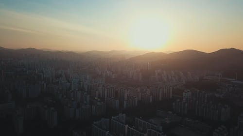 A City Gets Sunlight From The Sun Rising Behind The Mountains