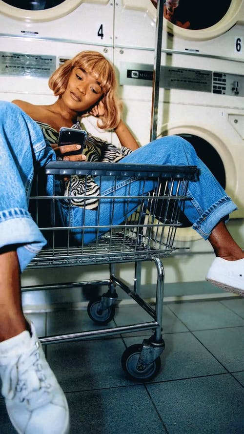 Woman Sitting In A Shopping Cart While Waiting In A Laundry Shop