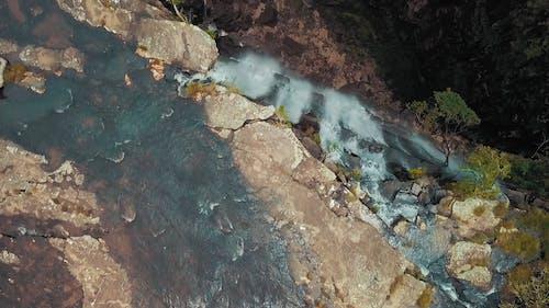 Водопады высоко над горными скалами проливаются ливнями в долину скалистой реки