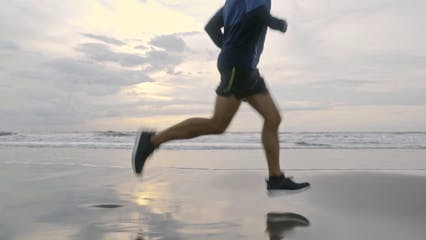 A Man Running On The Beach Shore
