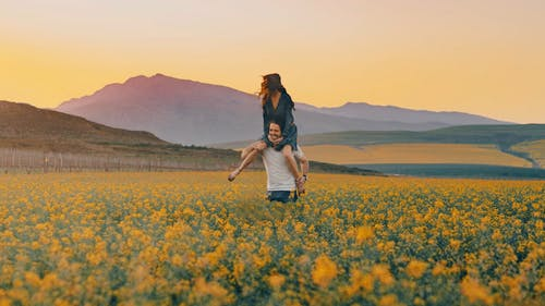 A Man Carrying A Woman On His Shoulders Having Fun In A Flower Field