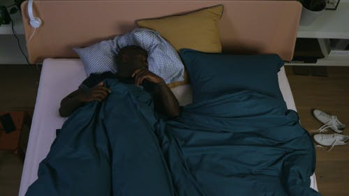 A Man Trying To Fall Asleep In A Bedroom