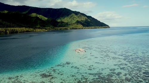 Aerial Footage Of People Swimming Around A Boat Docked In Shallow Crystal Clear Waters Near Beautiful Green Mountains