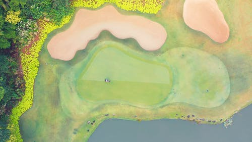 Aerial View Of A Man Cutting The Grass Of A Golf Course