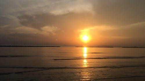 Вид на восход солнца над горизонтом с берега пляжа
