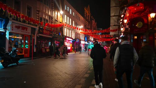 People Walking In A Street With Lanterns Hanging Above For Attraction