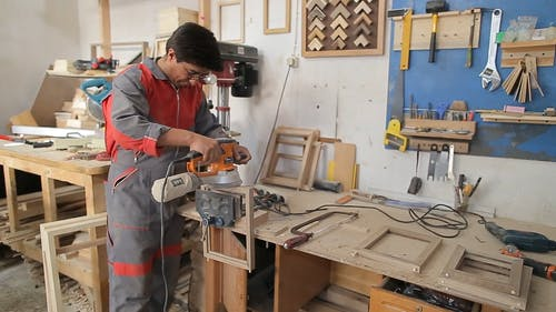 A Man Working In A Wood Workshop Making Frames