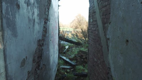 A Narrow Alley In Between Two Concreted Dilapidated Walls