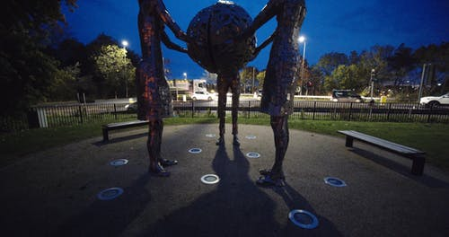 Three Women Sculptures In A Park Holding A Globe