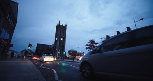 Cars Passing By A Street Where Church Bells Are Ringing