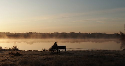 A Person Sitting Alone On A Bench In Front Of A Lake