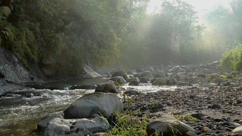 A Rocky River With Rays Of Sunlight