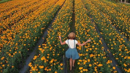 Woman Running In A Field Of Flowers