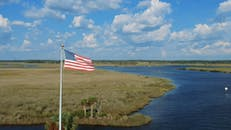 An  American Flag Swaying In A Pole Over A River Swamp