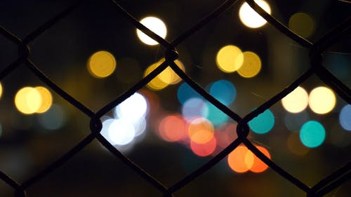 Close Up Shot Of A Square Wired Fence Causing The Background Lights To Be Out Of Focus