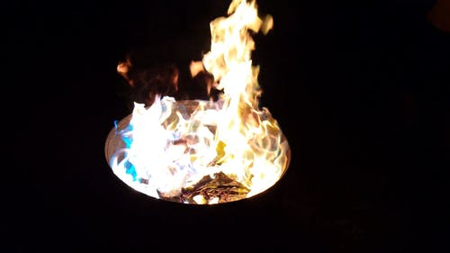 Burning Scrap Material In A Metal Drum In The Darkness Of Night