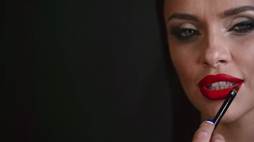 A Woman Putting On Red Lip Color Using A Lip Brush
