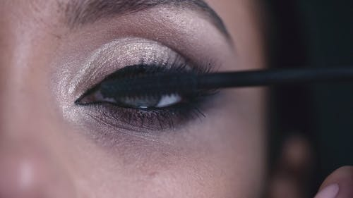 A Woman Applying Mascara To Thickens And Enhanced Her Eye Lashes