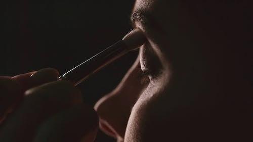 A Woman Applying An Eye Shadow Makeup On Her Eyelid