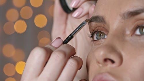 A Makeup Artist Applying Makeup On A Woman's Eyebrow