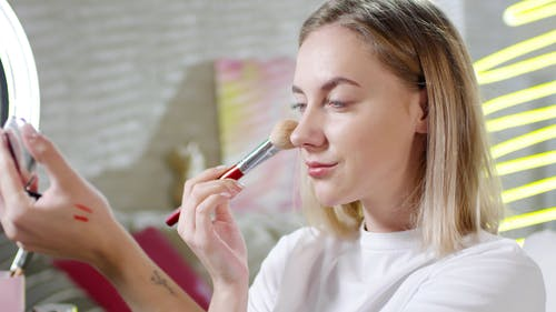 A Woman Using A Brush For Makeup Application