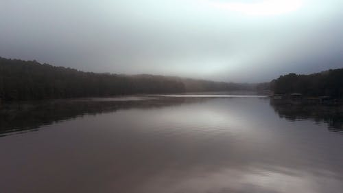 A Lake With Calm Waters On A Foggy Day