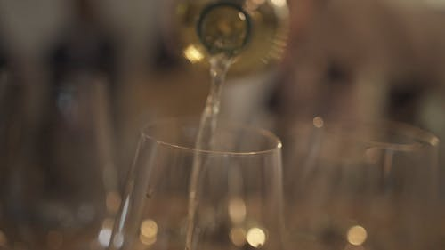 Pouring White Wine On Crystal Glasses
