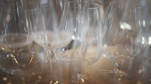 Pouring White Wine On Wine Glasses In Row