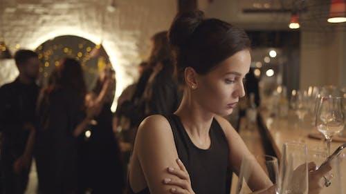 Una Mujer Sentada En Un Bar Con Un Grupo De Personas Bailando Detrás