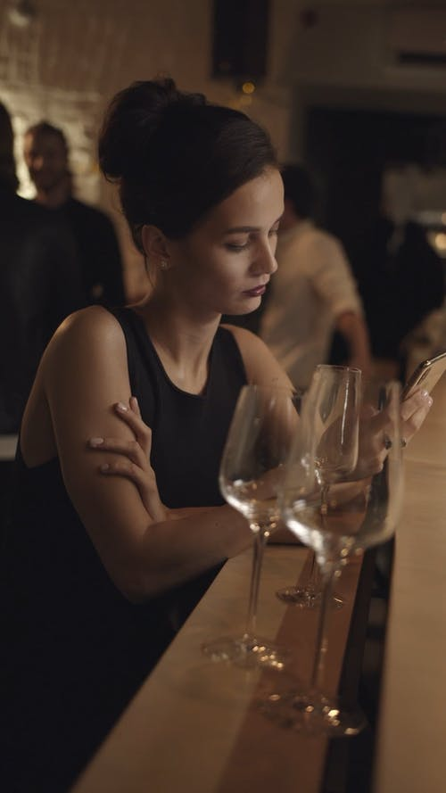 A Woman Leaves A Bar After Looking At Her Cellphone